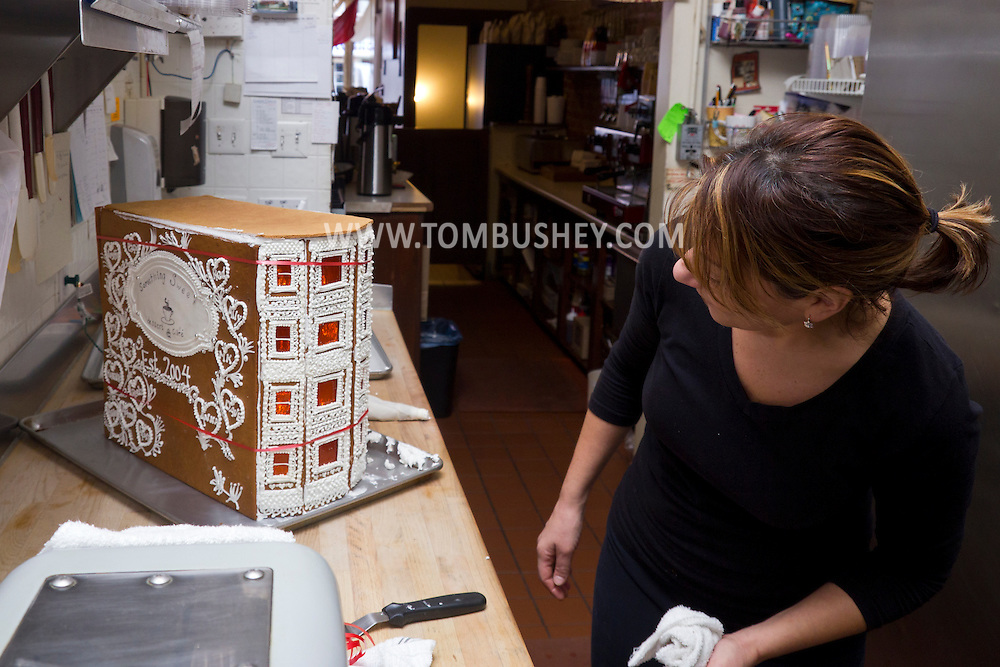 Middletown, New York - A baker looks over a gingerbread house she made at Something Sweet Dessert Cafe on  Nov. 23, 2014. ©Tom Bushey / The Image Works
