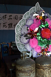 "China, Beijing, Chaoyang, San Jian Fang, 2008. A wreath usually reserved for funerals is displayed inside a restaurant protesting forcible eviction. The Chinese characters read: ""han wei guo jia"" or ""protect country"" and ""shi si wei hu"" or ""pledge our lives.""."