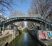 Passerelle de la Grange-aux-Belles, a cast iron arched pedestrian footbridge built late 19th century in the Marais basin, and the Ecluses des Recollets lock, between the Quai de Valmy and Quai de Jemmapes, over the Canal Saint-Martin in the 10th arrondissement of Paris, France. The footbridge is positioned next to the Pont Tournant de la Grange-aux-Belles, a road bridge which rotates to allow canal boats to pass. The Canal Saint-Martin is a 4.6km long waterway between the Canal de l'Ourcq and river Seine, built 1802-25 to provide a fresh water source to the city and provide a trade route for canal barges. Picture by Manuel Cohen