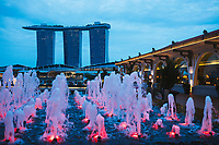 A view over fountains and the water with Marina Bay Sands, one of Singapore's most famous modern landmarks.