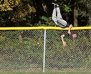 Scotchtown, New York -  A player climbs over the outfield fence to retrieve home run balls during the Wiffle for Kids charity Wiffle Ball tournament at the Town of Wallkill Little League fields on Sept. 25, 2010. The annual event is run by the Wallkill East Rotary. ©Tom Bushey / The Image Works