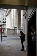 City people shelter from rain in the privacy of a dark corner to check messages, by Cornhill in the City of London, the capital's financial district, 7th March 2018, in London England.