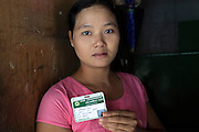 A Burmese worker shows her ID in a factory in Mae Sot , Thailand.