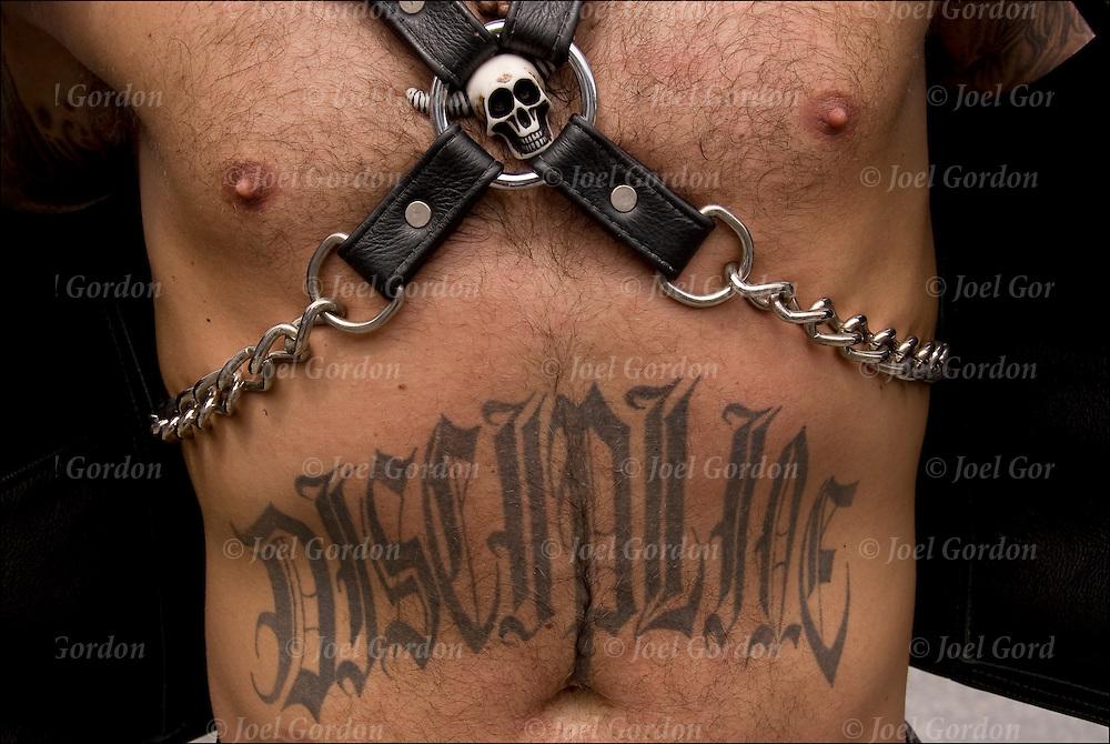 "Tattoo ""Discipline"" on abdomen with S&M skull paraphernalia and leather @ Folsom Street S&M street fair"