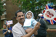 A man holding a baby waving a Union Jack flag enjoying a Golden Jubilee street party in Jubilee Street in the Stepney Green area of east London, where hundreds turned out to celebrate the 50 year reign of Queen Elizabeth II. Celebrations took place across the United Kingdom with the centrepiece a parade and fireworks at Buckingham Palace, the Queen's London residency. Queen Elizabeth ascended to the British throne in 1952 upon the death of her father, King George VI.