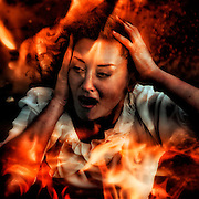 a woman looking through flames, screaming