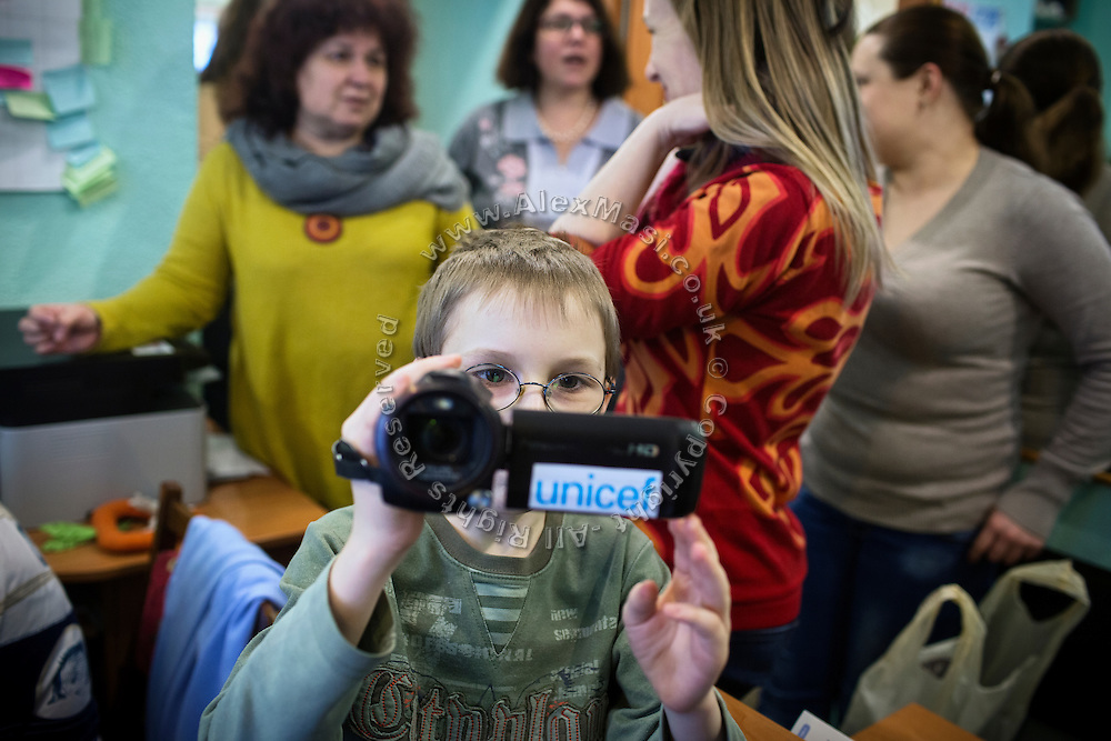 Yaroslav, 10, is using his UNICEF video-camera while visiting 'Ukrainian Frontiers', inside a community meeting place in support of internally displaced persons. (IDPs) Yeroslav is taking part to the UNICEF-sponsored One Minute Junior project for internally displaced persons (IDPs), carried out by the local NGO 'Ukrainian Frontiers' in the city of Kharkiv, the country's second-largest, in the east. The conflict between Ukrainian army and Russia-backed separatists nearby, in the Donbass region, have left more than 10000 dead since April 2014, including over 1000 since the shaky Minsk II ceasefire came into effect in February 2015. The approximate number of people displaced by the conflict is 1.4 million as of August 2015. Yeroslav's mother, Olga, is also a participant to a different project of 'Ukrainian Frontiers', called 'Self-Employment', first as a beneficiary, and now as a paid hotline coordinator for people seeking jobs and formation courses.