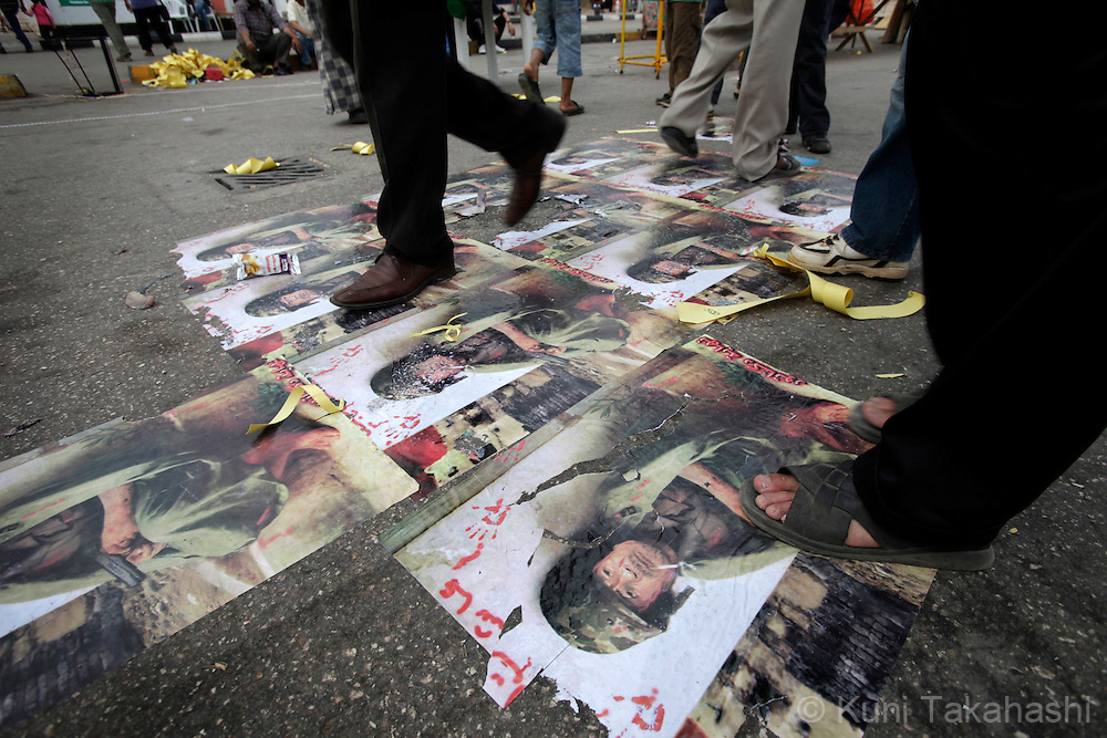 People step over posters of Moammar Gadhafi in Benghazi, Libya on May 22, 2011. In a boost to Libya's rebels against Gadhafi, the European Union opened a diplomatic office Sunday in their eastern stronghold Benghazi and pledged support for a democratic Libya. Photo by Kuni Takahashi