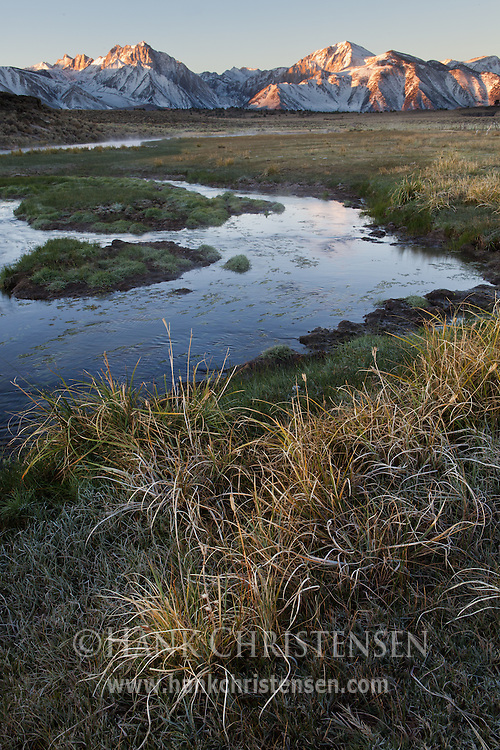 Grass adorns the banks of Hot Creek as sun touches the mountains to the east