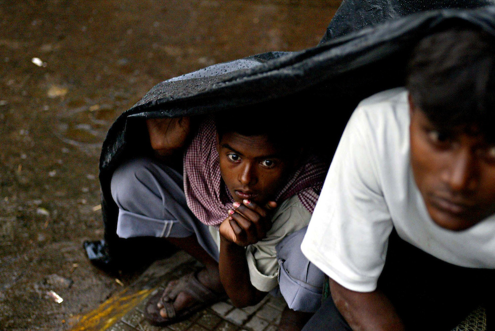 Two men shelter from the rain in Old Delhi, India .