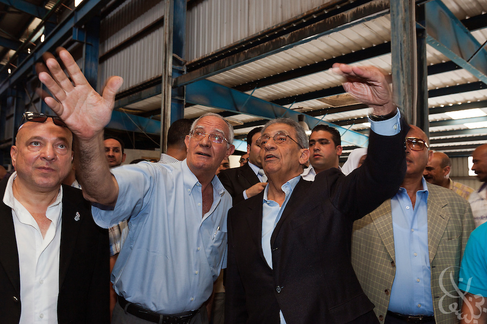 Egyptian Presidential candidate Amr Moussa (center right) tours a recycling plant in the Nile Delta region near the city of Banha May 5, 2012. Moussa has made the economy one of his campaign's central emphasis, promising to return it to strong growth in a short time frame through support for industry and trade.