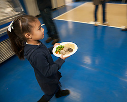 Scenes of  the Santa Rosa French-American Charter School in Santa Rosa,  California . A student carries her lunch in the Cafe.