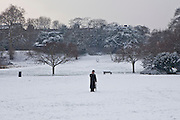 An Orthodox Jewish man on a mobile phone in a snowy January at Springfield Park, Stamford Hill, London.