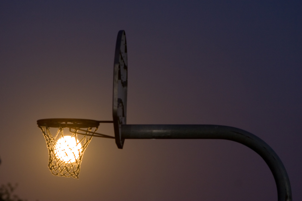 A full moon rises over the Illinois prairie, seen through the net of a basketball hoop on a small town playground.