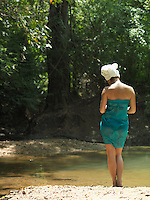 Young woman lake in forest with towel wrapped on head back view
