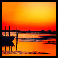 Captree , NY, March 8, 2015:  The sun sets on Captree Island in Suffolk County, Long Island. A boat an some moorings are silhouetted against the brilliant red orange sky.  © Audrey C. Tiernan