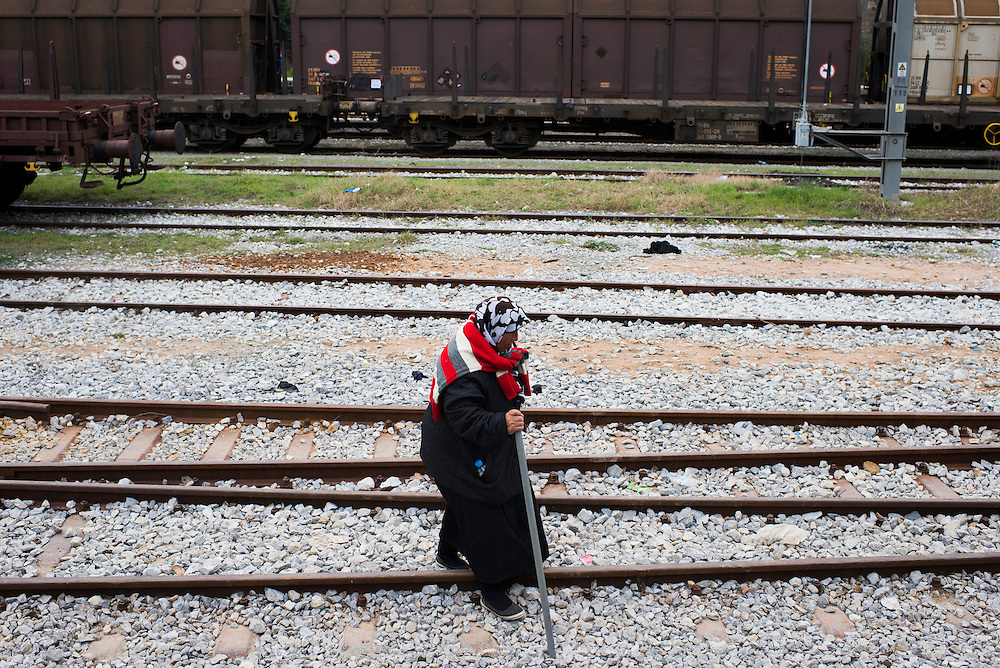 An elderly refugee makes her way along the railroad tracks to a refugee camp on the Macedonian (FYROM) border on March 6, 2016 in Idomeni, Greece.