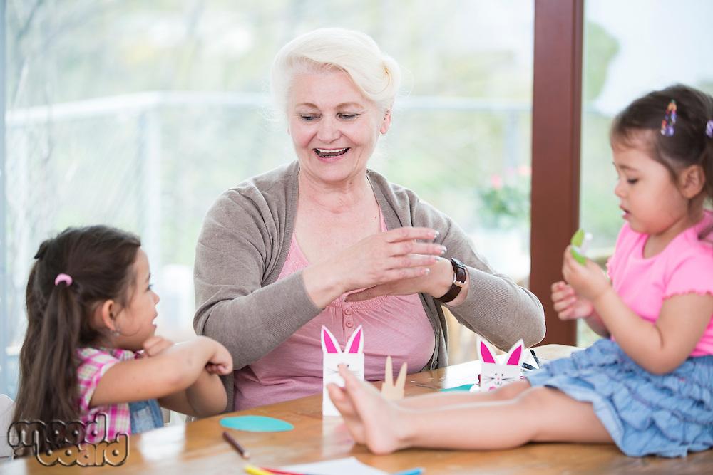Senior woman assisting granddaughters in art work at home