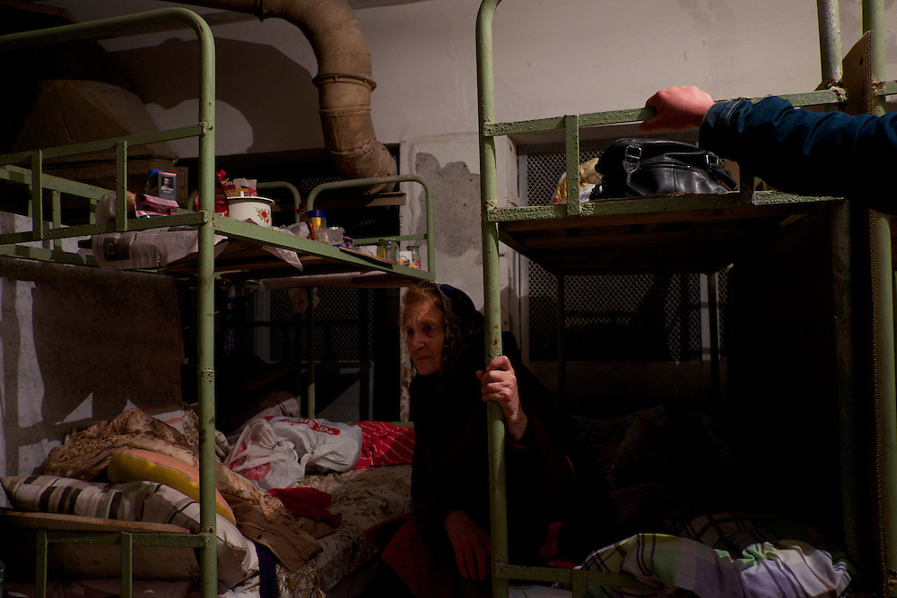 DONETSK, UKRAINE - OCTOBER 21, 2014: Valentina Georgiyevka, an 85 year old resident from Donetsk, sits in one of the many beds at a improvised bomb shelter in the basement of an old typography in Kievskiy district. Valentina moved to the shelter together with her daughter, around four months ago, after getting her house partially destroyed during fighting between DNR separatist combatants and the Ukrainian National Guard. CREDIT: Paulo Nunes dos Santos