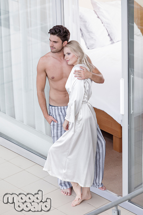 Full length of loving young couple spending quality time at balcony doorway