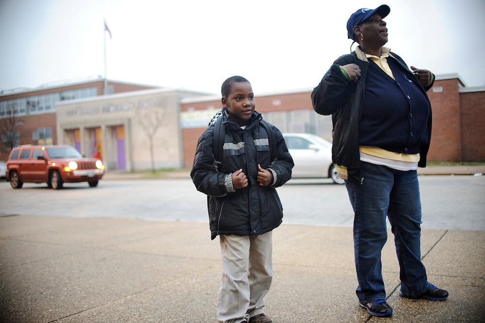 Photo copyright 2009, Matt Roth<br /> Wednesday, February 29, 2012<br /> <br /> City Springs Elementary School first grader Jahmal Harrison, and his mother Tameka Harrison, wait across the street from his school for the 11 bus to their shelter Wednesday, February 29, 2012. Tameka, who can't work due to a facial injury, volunteers at her son's school where poverty is the norm. Ninety-six percent of the student body qualifies for free lunches. Tameka and Jahmal, who suffers from lead poisoning, used to live in one of the close-by housing projects, but have been homeless for the last two months. They're currently staying at Sarah's Hope Shelter in West Baltimore. Tameka thought she was going to be moving into an apartment Friday, under the auspices that both the security deposit and the first month's rent would be waived, but the latter was not. So, they're staying in the Sarah's Hope shelter a little while longer.