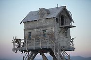 Baba Yaga's House by: Jessi Sprocket Janusee and Baba Yaga's Book Club from: Reno, NV year: 2018<br /> <br /> The house of Baba Yaga will rise from the playa straddling it's mechanical chicken legs. The crone's house will be poised to run at the slightest provocation. Ascend her staircases to test the old witch if you dare. Are you able to walk through the veil of mortality into the space where the seer dwells? If you are strong of will, feeling bold and willing to show vulnerability she may allow you to venture within her sanctum.<br /> <br /> URL: http://jessisprocket.com/baba-yaga/