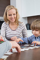 Boy playing cards with parents at home