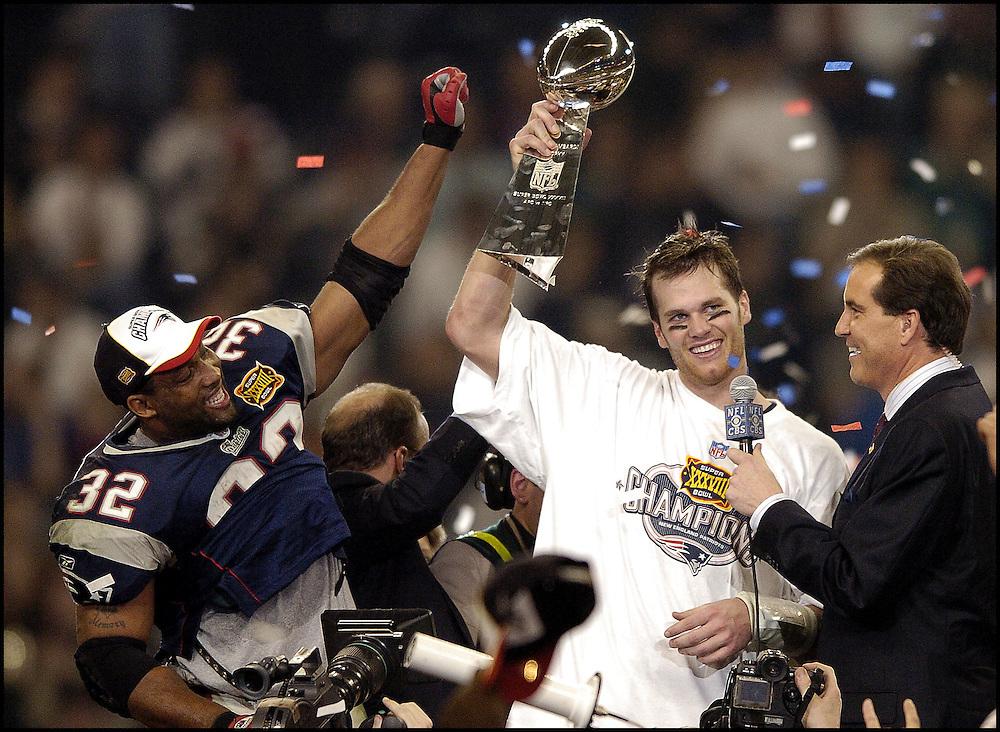 (2/2/04Houston, TX) Super Bowl XXXVIII. New England Patriots. Tom Brady holds up the Lombardi Trophy as Antowain Smith celebrates the win. (020104patsmjs-staff photo by Michael Seamans. Saved in photo Monday/cd)