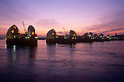 Ageing 80s technology of the Thames Barrier on the River Thames near Woolwich in east London. As daylight fades to become a purple hue, we see the waters of the Thames flowing on the tide. Operational in 1982, the Thames Barrier is one of the largest movable flood barriers in the world, managed by the UK's Environment Agency. The barrier spans 520 metres across the River Thames near Woolwich, and it protects 125 square kilometres of central London from flooding caused by tidal surges.  The barrier has closed over 80 times since the year 2000 with 'at least 800,000 homes and businesses have protected from tidal surges.