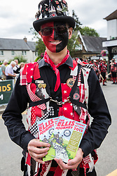 Datchet, UK. 30 June, 2019. A member of Datchet Border Morris, an all male Border Morris side with a mixed band who perform dances in the English border Morris style, poses with a programme before the arrival of pre-1905 vehicles taking part in the 48-mile Ellis Journey from Micheldever station near Winchester to Datchet. The Ellis Journey is a reenactment of the first recorded journey by a motorised carriage in England undertaken by pioneer automobilist Hon. Evelyn Ellis in his new, custom-built Panhard-Levassor on 5th July 1895.