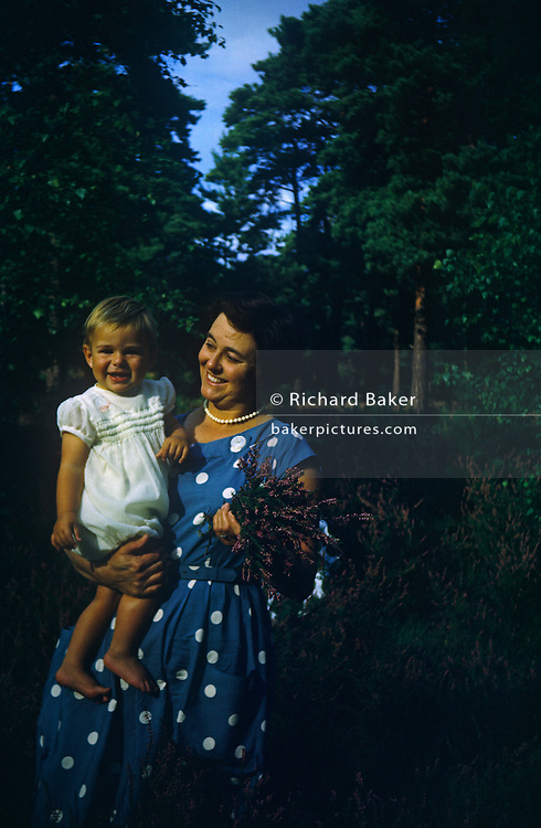 A portrait of a mother in her 41st year has been gathering heather in handfuls and holds up her young child who grins towards his father who is taking the picture at a park near the Essex seaside town of Southend. It is the summer of 1960 and the mum's dress is styled from the previous decade: blue with white spots and pearl necklace. She too is smiling as she grasps the flowers and her child on a warm day. Oddly, the boy looks as though he is wearing a girl's dress which may have been a hand-me-down from an older sibling or just the trend then.