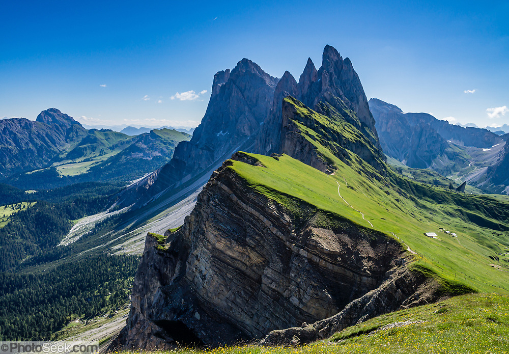 Sharp spires of the Geisler/Odle Group soar above green Alpe di Seceda, above St. Christina and Ortisei, in South Tyrol, the Dolomites, Italy, Europe. The beautiful ski resort of Selva di Val Gardena (German: Wolkenstein in Gröden; Ladin: Sëlva Gherdëine) makes a great hiking base in the Trentino-Alto Adige/Südtirol (South Tyrol) region of Italy. For our favorite hike in the Dolomiti, start from Selva with the first morning bus to Ortisei, take the Seceda lift, admire great views up at the cross on the edge of Val di Funes (Villnöss), then walk 12 miles (2000 feet up, 5000 feet down) via the steep pass Furcela Forces De Sieles (Forcella Forces de Sielles) to beautiful Vallunga (trail #2 to 16), finishing where you started in Selva. The hike traverses the Geisler/Odle and Puez Groups from verdant pastures to alpine wonders, all preserved in a vast Nature Park: Parco Naturale Puez-Odle (German: Naturpark Puez-Geisler; Ladin: Parch Natural Pöz-Odles). UNESCO honored the Dolomites as a natural World Heritage Site in 2009.