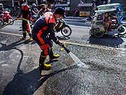 23 JANUARY 2018 - CAMALIG, ALBAY, PHILIPPINES: A Camalig firefighter cleans ash off the main street after an ash fall caused by an eruption of the Mayon volcano. The Mayon volcano continued to erupt Tuesday, although it was not as active as it was Monday. There were ash falls in communities near the volcano. This is the most active the volcano has been since 2009. Schools in the vicinity of the volcano have been closed and people living in areas affected by ash falls are encouraged to stay indoors, wear a mask and not participate in strenuous activities.    PHOTO BY JACK KURTZ