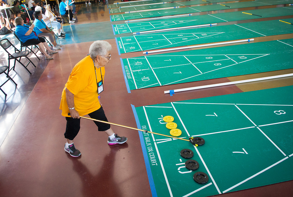 "mkb071917b/metro/Marla Brose --  Sue Perea of Laguna takes a shot while competing in the New Mexico Senior Olympics State Summer Games' women's singles shuffleboard competition inside Sid Cutter Pilot's Pavilion at Balloon Fiesta Park in Albuquerque, N.M., Wednesday, July 19, 2017. The pavilion is lined with about 16 shuffleboard courts for about 150 competitors. ""Try to stay out of the kitchen,"" Perea explained about her shuffleboard strategy. The ""kitchen"" refers to the squares at the end of the court where disks inside score -10 points. Perea just returned from the National Senior Games shuffleboard competition in Birmingham, Alabama. The shuffleboard competition continues through Friday and the State Summer Games continue through Sunday. (Marla Brose/Albuquerque Journal)"