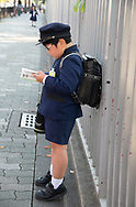 A young school boy dressed in a military style uniform with shorts in Kyoto,  Japan