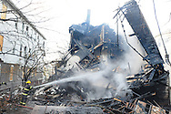 A fire fighter hoses down the smoldering remains of the back of 44 Arlington St. (CHRIS CHRISTO)