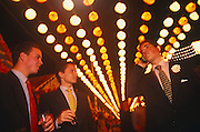 Three young men are seen from a very low angle as they make arrangements with other friends to meet at the Spring Feria in Seville, Spain. Beneath dozens of colourful lights which hang from cables above their heads, two stand holding drinks while the third speaks into his mobile phone. They are all impeccably dressed in smart jackets and tasteful ties with one owning a carnation in his lapel. It is a lively event that Seville holds annually in the vast fairground area on the far bank of the Guadalquivir River. Rows of temporary marquee tents, or casetas, host families, corporations and friends into the late hours during the April Fair which begins begins two weeks after the Semana Santa, or Easter Holy Week in the Andalusian capital.