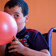Khalid receives one on one instruction in the Mercy Corps resource room. Here he blows up a balloon—part of his lesson is dedicated to exercises to improve his lung function, to help prevent respiratory failure, a common cause of death with children who have muscular dystrophy. Zaatari camp for Syrian refugees, Jordan, April 2015.