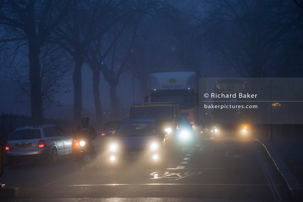 Commuter traffic and pedestrians at dawn on a foggy morning in south London.