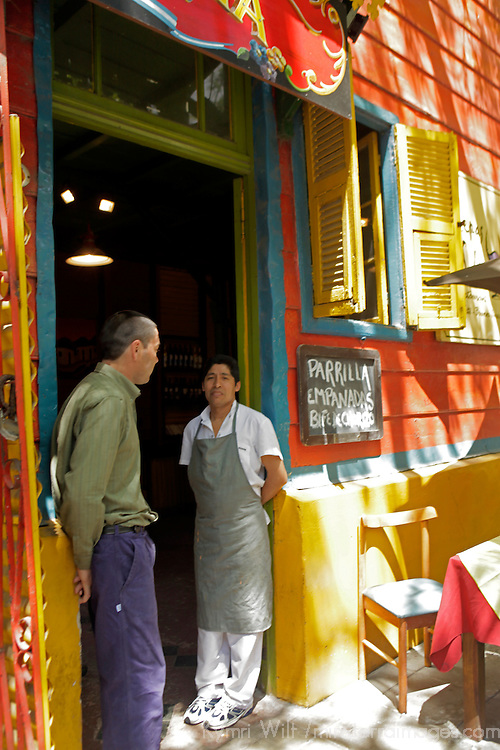 South America, Argentina, Buenos Aires. Parilla grill chef having conversation in doorway of La Boca restaurant.