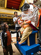 """05 SEPTEMBER 2016 - BANGKOK, THAILAND:   Men unload a statue of Ganesha on the first day of Ganesha Chaturthi celebrations at Shiva Temple in Bangkok. Ganesha Chaturthi also known as Vinayaka Chaturthi, is the Hindu festival celebrated on the day of the re-birth of Lord Ganesha, the son of Shiva and Parvati. The festival, also known as Ganeshotsav (""""Festival of Ganesha"""") is observed in the Hindu calendar month of Bhaadrapada. The date usually falls between 19 August and 20 September. The festival lasts for 10 days, ending on Anant Chaturdashi. Ganesha is a widely worshipped Hindu deity and is revered by many Thai Buddhists. Ganesha is widely revered as the remover of obstacles, the patron of arts and sciences and the deva of intellect and wisdom.    PHOTO BY JACK KURTZ"""