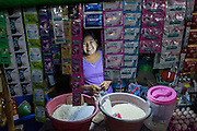 Woman selling shampoo, rice and other goods, Pathein