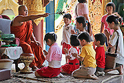 Children in prayer inside the Dhammikarama Burmese Buddhist Temple where people meet with the priests. Located on Penang, Malaysia.