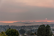Looking west across San Francisco Bay from the East Bay hills with Golden Gate Bridge to left as the sun sets through wildfire smoke over the Marin Headlands, south of the Sonoma and Napa wildfires. Air quality on this day was rated as bad in San Francisco as in Beijing China. 12th October, 2017.
