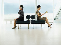 Businesswomen Sitting on Benches facing opposite directions talking on mobile reading newspaper profile