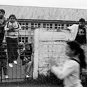 Children and young teenagers play in a housing estate in the heart of the small Romanian town of  Copsa Mica, Transylvania, Romania. Copsa Mica was once described as the most polluted town in Europe. May 8, 2008 Photo Tim Clayton...Copsa Mica, a small industrial town deep in Transylvania, Romania, was described during the 1990s as the most polluted town in Europe with lead levels reaching were more than 1000 times the allowable International limits and life expectancy nine years shorter than the National average...The pollution was caused entirely by two factories, Carbosin produced black for dies and tires and closed in 1993 while Sometra, a nonferrous smelter is still operational today...The pollution was so bad sheep were black, covered in soot and health officials advised against eating livestock or vegetables and drinking the water or milk...The Communist rule of Nicolae Ceausescu is blamed for the widespread environmental degradation that left industrial parts of Romania in ecological disaster. Industry was situated in a way to concentrate pollution in small areas leaving the rest of the country relatively free of pollution. Copsa Mica in particular was left an environmental disaster...The pollution caused a direct affect on human health with widespread Lung disease, Impotency, the highest infant mortality rate in Europe, Lead poisoning and behavioral problems...Fifteen years on since the closure of Carbosin in 1993, the factory skeleton remains as part of the towns bleak landscape, Unfinished communist style housing blocks still stand in the heart of the towns housing estate. The town's inhabitants are still trying to recover from the long lasting effects of pollution...Recent survey's found the soil contained so much lead that it was 92 times above the permitted level; the vegetation had a lead content 22 times above the permitted level. While toxins have penetrated at least one meter (three feet) into the soil leaving the entire food cha