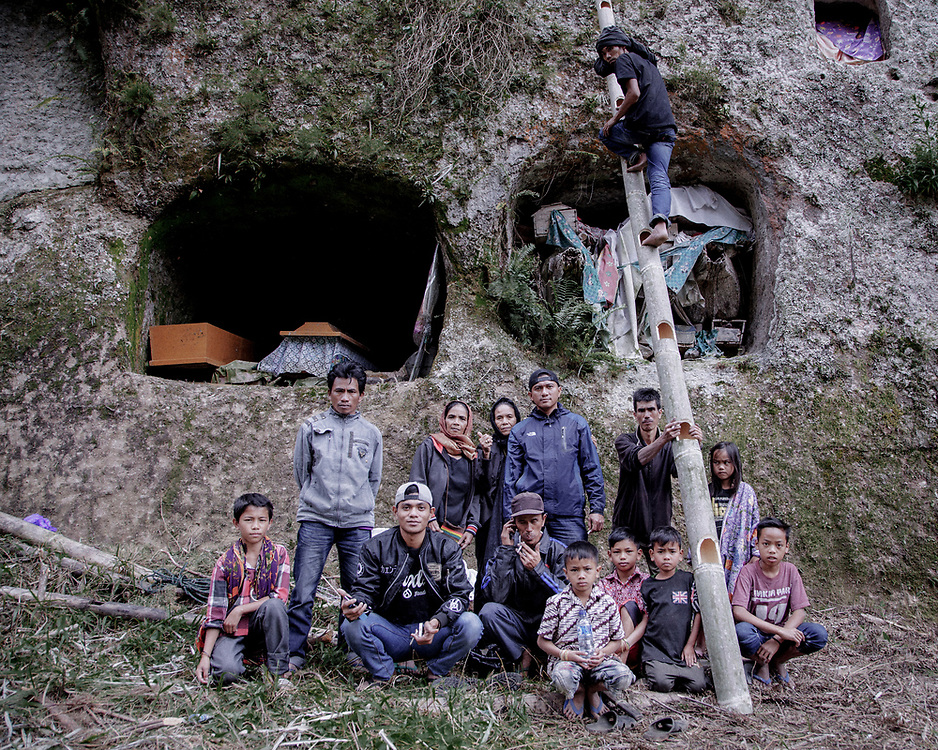 Family members pose for a portrait after adding a new layer of fabric to wrap the remains of a relative in Barrupu. In this district of Toraja, the body is not buried but placed in a hole carved into a cliff. <br />