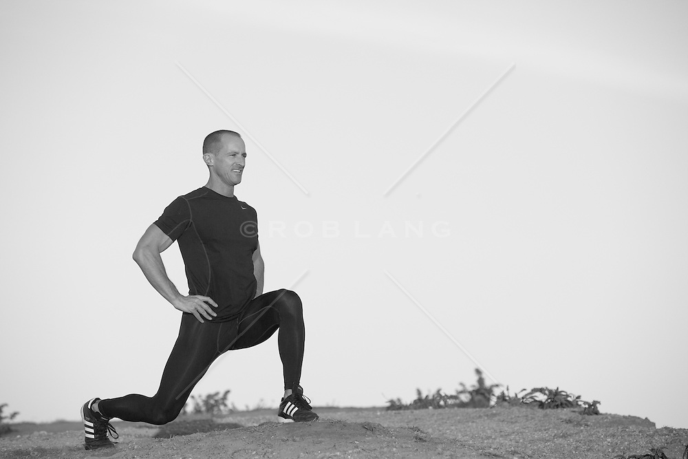 handsome middle aged man stretching and working out outdoors