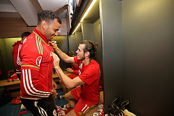 CARDIFF, WALES - Tuesday, October 13, 2015: Wales' Gareth Bale signs Hal Robson-Kanu's shirt in the dressing room after the 2-0 victory over Andorra, and qualification for the finals, following the UEFA Euro 2016 qualifying Group B match at the Cardiff City Stadium. (Pic by David Rawcliffe/Propaganda)