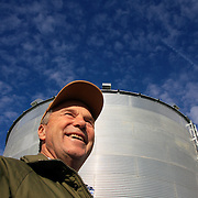Bill Johnson represents the fourth generation that has farmed his family run farm, purchased by his great grandfather in 1887.  Johnson has farmed most of his life, starting as a teenage boy in Shelby County, Iowa.  One of his largest storage bins (behind Johnson) holds 27,000 bushels of corn. <br />    Johnson also has eight tractors in sheds around his farm, as well as a planter, combine and grain wagon.  He and his wife, Karen, have written two books on farming, drawing from journals they've kept since their marriage in 1969. Photo by David Peterson